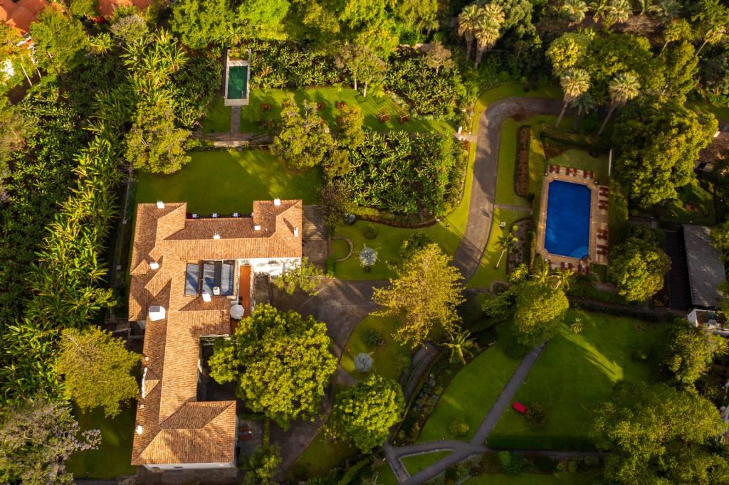 Imagem aérea de uma casa branca cercada de jardins, com uma piscina maior, azul, e uma menor, verde