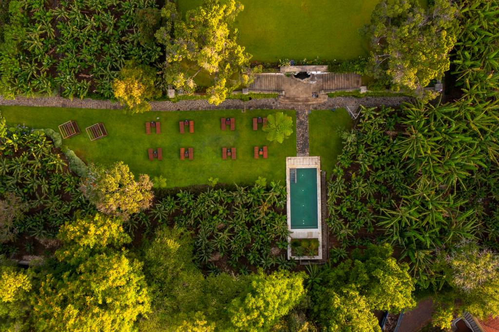 Imagem aérea de um jardim com uma piscina e um gramado com espreguiçadeiras