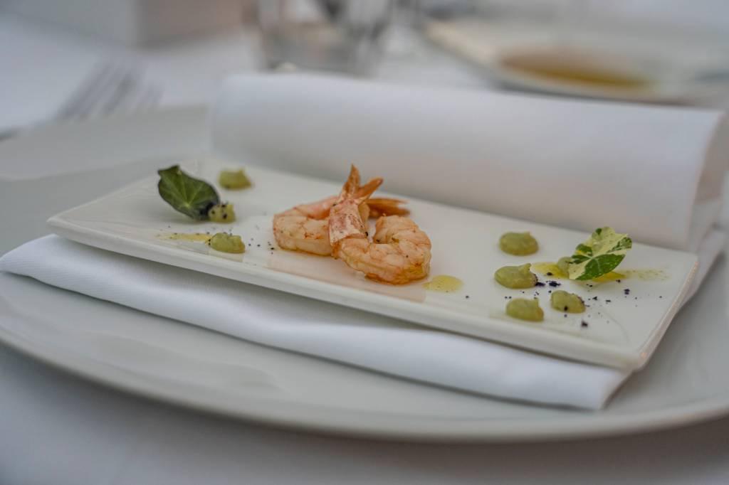 Prato branco com dois camarões e um molho verde na mesa do restaurante