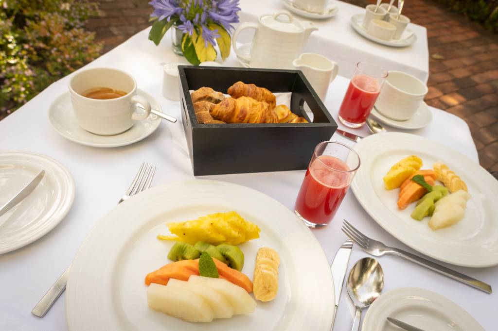 Mesa de café da manhã com prato de frutas, suco vermelho nos copos e cesta de croissants