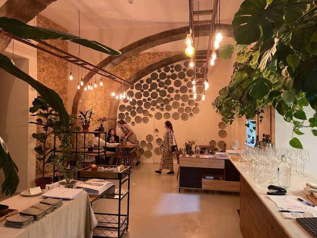 Salão de um restaurante com mesas vazias, plantas à direita, objetos redondos decorando a parede do fundo e uma pessoa a passar na frente.