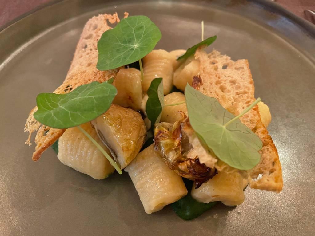 Prato cinza com quadradinhos de gnocchi e algumas folhas de capuchinha por cima