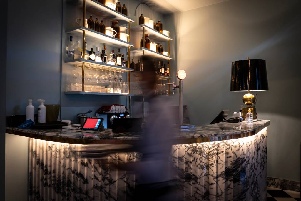 Bar com um balcão escuro de mármore e uma pessoa passando na frente, desfocada