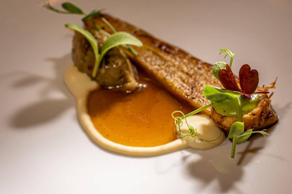Prato branco com uma fatia de berinjela, um caldo marrom e um purê bege ao lado, com folhas verdes por cima