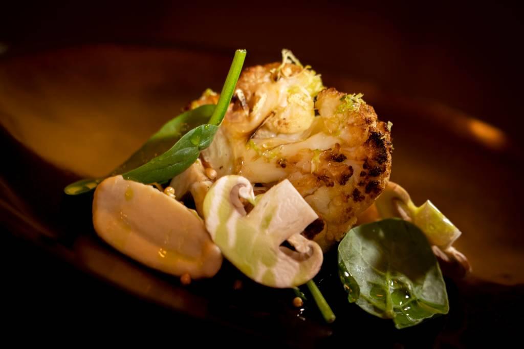 Prato de restaurante onde se pode ver um pedaço de couve-flor, um cogumelo e folhas verdes