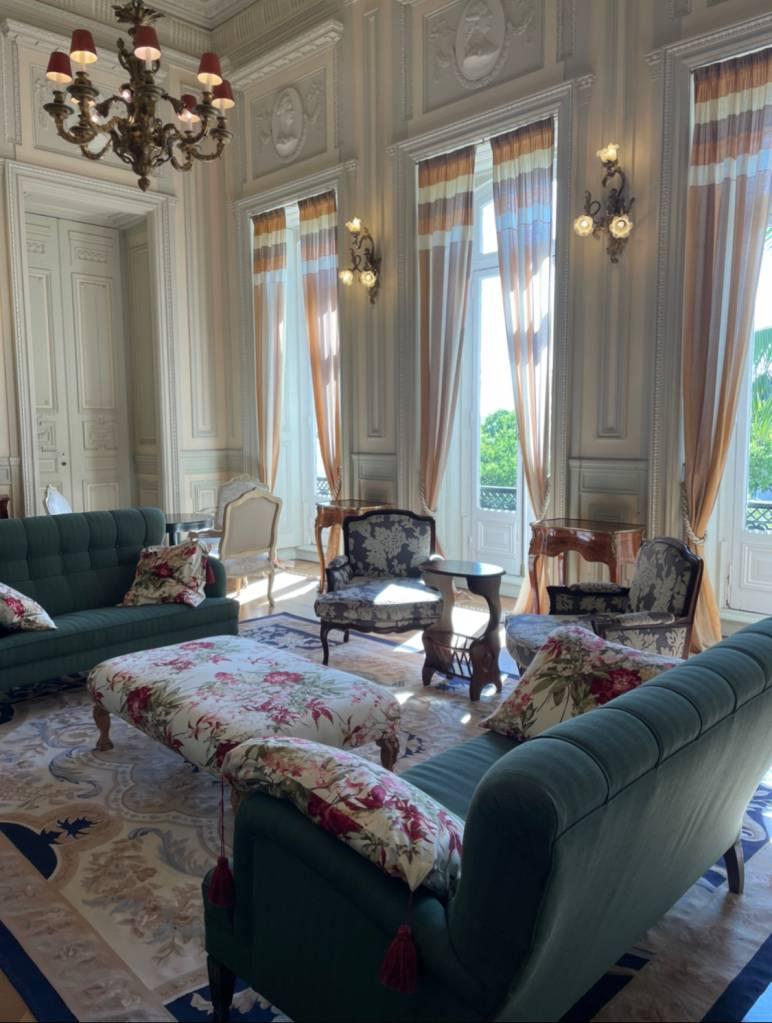 Sala decorada com móveis de época: sofás azuis, poltronas floridas e duas janelas com cortinas até o chão
