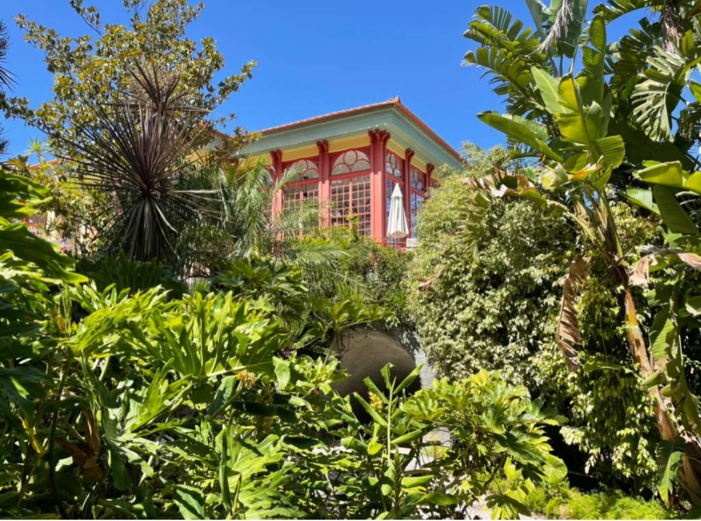 Jardim tropical com plantas exuberantes e uma construção de ares orientais ao fundo, com colunas vermelhas