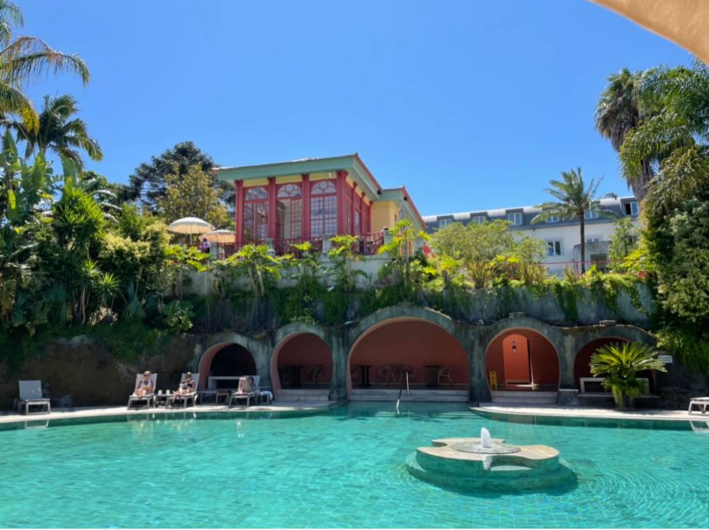 Uma piscina com uma fonte no meio e algumas espreguiçadeiras com pessoas em volta, uma varanda com arcos ao fundo e, no alto, plantas e uma construção com colunas vermelhas