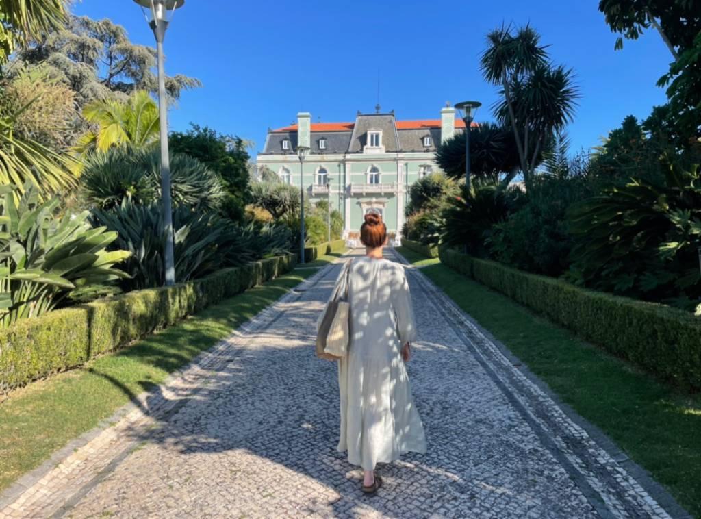 Uma mulher de coque e vestido verde caminha em uma alameda cercada de plantas, com um palacete histórico ao fundo