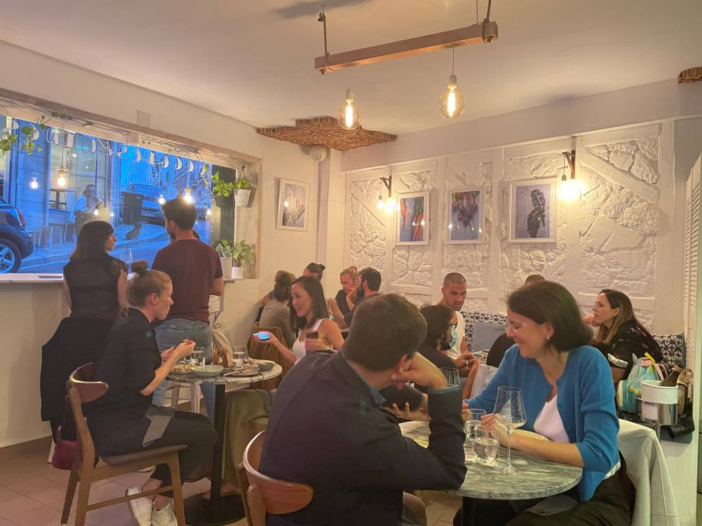 Salão de um restaurante com mesas redondas e pessoas sentadas