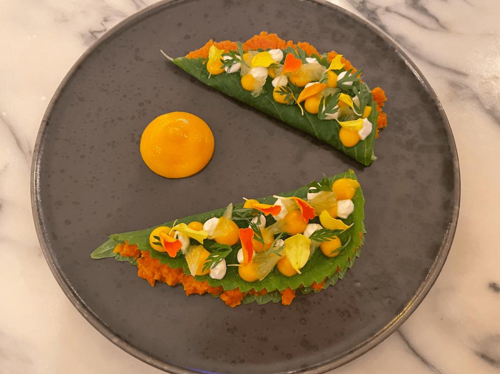 Prato cinza com duas folhas recheadas de creme laranja e decoradas com bolinhas de cremes coloridos, um creme de laranja entre elas