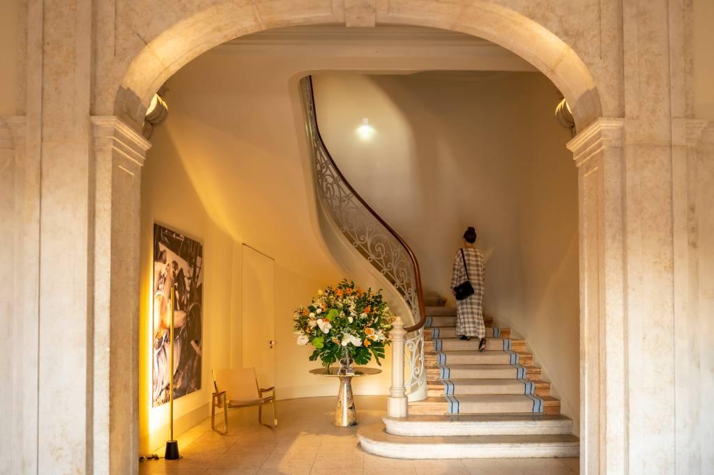 Mulher com vestido branco longo e bolsa preta subindo uma escada em curva, com um grande vaso de flores ao lado