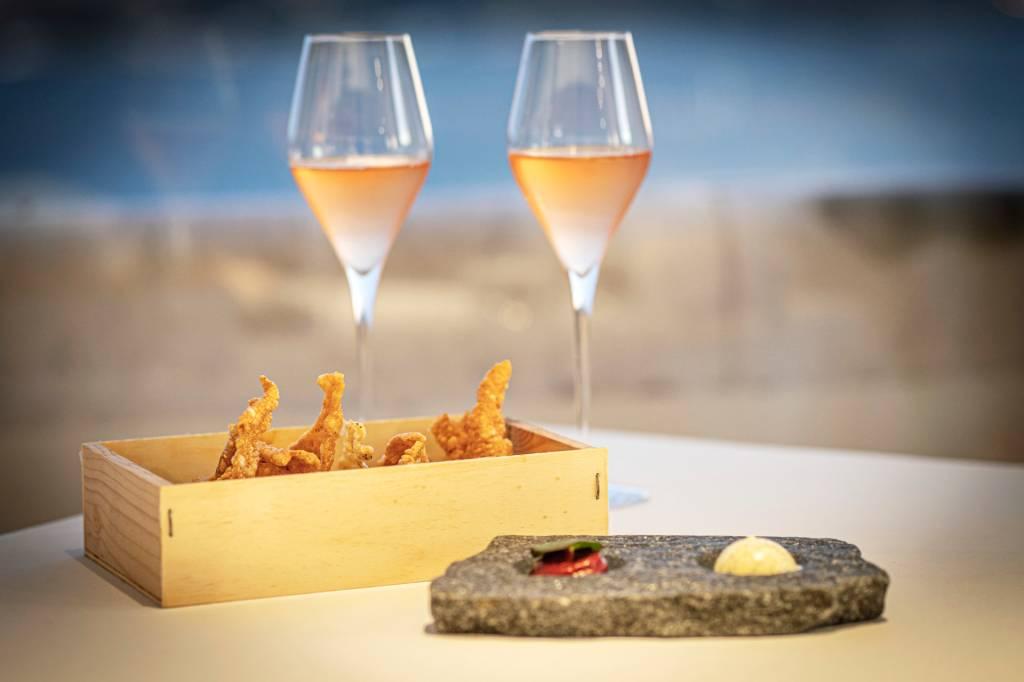 Duas taças de espumante rosé ao fundo e, em primeiro plano, um prato de pedra cinza com manteigas e uma caixa de madeira com crisps de arroz