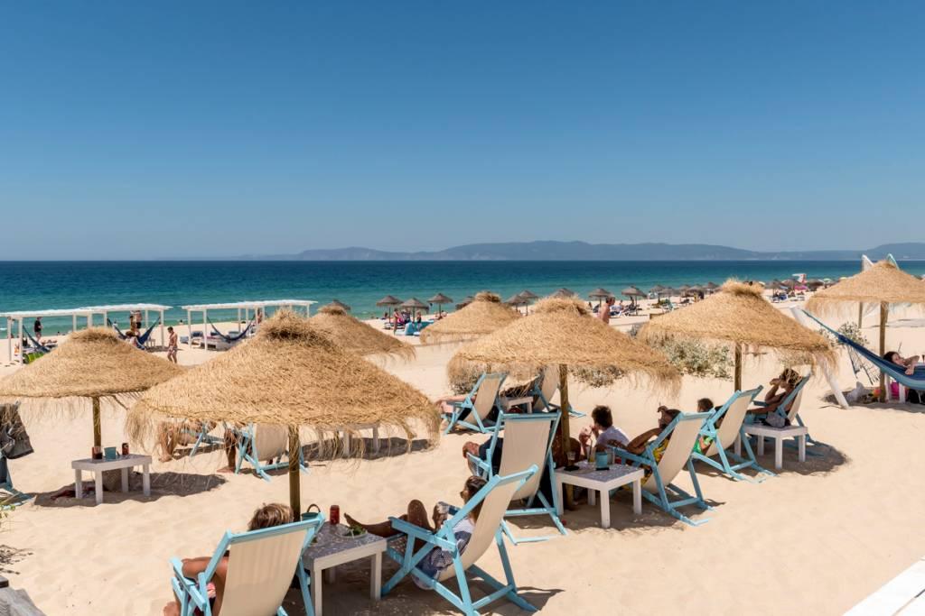 Espreguiçadeiras com guarda-sóis de palha e cadeiras azuis na areia da praia, com o mar azul ao fundo