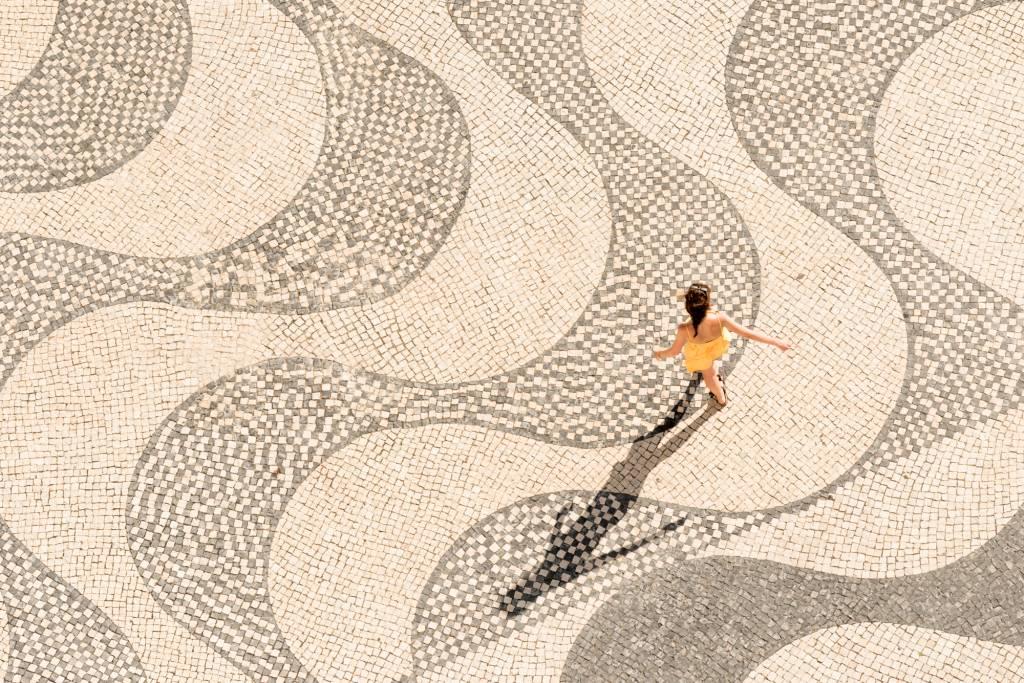 Menina de vestido amarelo anda de braços abertos sobre calçada portuguesa